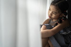 Depressed Little girl near window at home, closeup