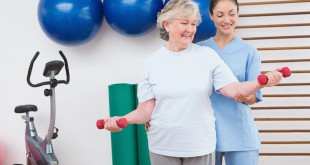 Therapist helping senior woman fit dumbbells in fitness studio