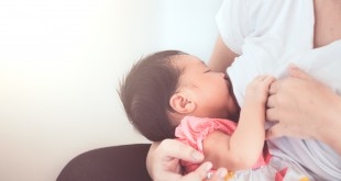 Mother breastfeeding her newborn baby girl. Baby happy while dri
