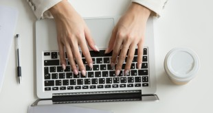 Businesswoman working on laptop, hands typing on keyboard, top v