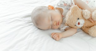 The newborn baby slept on a white bed and hugged the bear.