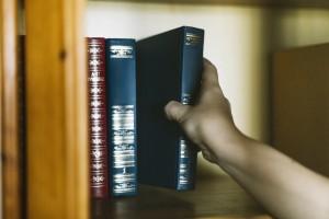 crop-hand-picking-book-from-shelf